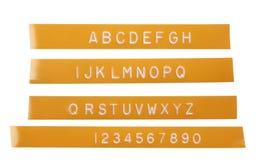 De brievenalfabet van de stempel op oranje etiketteringsband Stock Fotografie