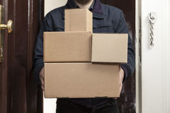 De brievenbesteller brengt met pakketten stock fotografie