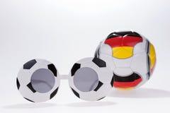 De bril van de voetbalsport en Voetbalbal met Duitse vlag Stock Fotografie