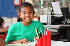 De briljante glimlach van het schoolmeisje bij haar bureau in klasse Stock Foto's