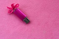 De briljante roze het geheugenkaart van de usbflits met een roze boog ligt op een deken van zachte en bont lichtrose vachtstof Kl stock foto's