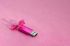De briljante roze het geheugenkaart van de usbflits met een roze boog ligt op een deken van zachte en bont lichtrose vachtstof Kl stock fotografie