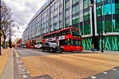 De Britse pictogrammen verdubbelen dekbus en taxi langs de Straat van Oxford in Londen, het UK Stock Fotografie