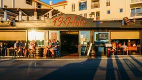 De Britse toeristen en expats ontspannen met één of ander dranken en gesprek bij het terras van een bar getiteld 19de gat Algarve Stock Foto's