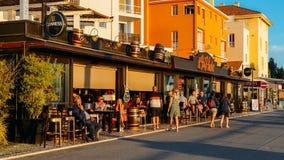 De Britse toeristen en expats ontspannen met één of ander dranken en gesprek bij het terras van een bar getiteld 19de gat Algarve Royalty-vrije Stock Afbeeldingen