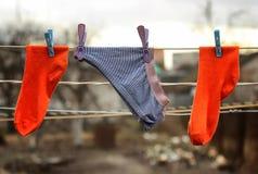 De broek en het paar sokken die op de kabel drogen maakten gekleurde wasknijpers vast openlucht Royalty-vrije Stock Afbeelding