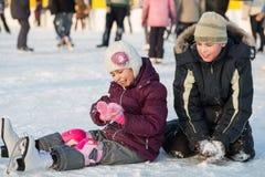 De broer en de zuster vielen samen terwijl het schaatsen Stock Foto