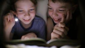 De broer en de zuster lezen een boek onder een deken met een flitslicht in een donkere ruimte bij nacht De jonge geitjes spelen stock footage