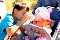 De broer geeft aan babymeisje aan drinkt water van een fles in een park royalty-vrije stock afbeeldingen