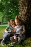 De broer met zuster van 7-9 jaar zit onder een boom en kijkt in de tablet Stock Foto's