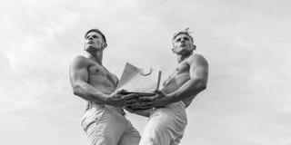 De broers kopen eco gezonde producten Dragen de kerels die aantrekkelijke tweelingen het winkelen zak uit pakpapier wordt gemaakt stock foto