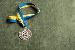 De bronsmedaille voor derde plaats met geel-blauw lint, exemplaar-ruimte stock foto
