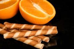 De broodjes en de sinaasappel van de chocoladewafel, op zwarte achtergrond stock afbeeldingen