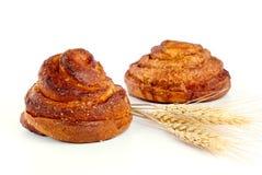 De broodjes van de kaneel met oor van tarwe Stock Afbeeldingen
