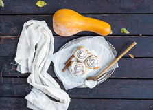 De broodjes van de kaneelpompoen met romig kaassuikerglazuur en rijpe pompoen stock foto's