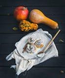 De broodjes van de kaneelpompoen met romig kaassuikerglazuur en rijpe pompoenen Royalty-vrije Stock Foto