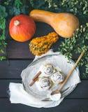 De broodjes van de kaneelpompoen met romig kaassuikerglazuur en rijpe pompoenen royalty-vrije stock foto's