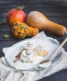De broodjes van de kaneelpompoen met romig kaassuikerglazuur en rijpe pompoenen royalty-vrije stock fotografie