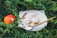 De broodjes van de kaneelpompoen met romig kaassuikerglazuur en rijpe ronde pu royalty-vrije stock afbeeldingen