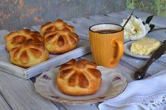 De broodjes van het karnemelkdiner in bloemvorm dienden met boter, mes en kop coffe op houten achtergrond Verse gebakken brioche  Royalty-vrije Stock Afbeeldingen