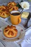 De broodjes van het karnemelkdiner in bloemvorm dienden met boter, mes en kop coffe op houten achtergrond Verse gebakken brioche  Stock Foto's