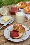 De broodjes van het karnemelkdiner in bloemvorm dienden met boter, mes, glas melk en jam op houten achtergrond Verse gebakken bri Royalty-vrije Stock Afbeeldingen