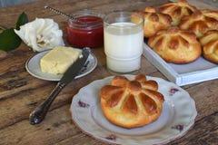 De broodjes van het karnemelkdiner in bloemvorm dienden met boter, mes, glas melk en jam op houten achtergrond Verse gebakken bri Stock Afbeelding