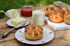 De broodjes van het karnemelkdiner in bloemvorm dienden met boter, mes, glas melk en jam op houten achtergrond Verse gebakken bri Royalty-vrije Stock Fotografie