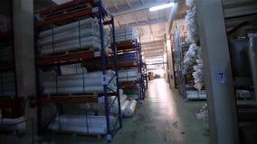 De broodjes van stoffen worden opgeslagen in het grondstoffenpakhuis, worden de regimenten gevuld met textiel, pakhuis van stoffe stock video