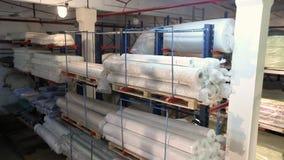 De broodjes van stoffen worden opgeslagen in het grondstoffenpakhuis, worden de regimenten gevuld met textiel, pakhuis van stoffe stock videobeelden
