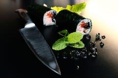 De broodjes van sushi op een zwarte lijst Royalty-vrije Stock Foto
