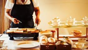 De broodrooster van het chef-kokgebruik voor het maken van ontbijt in het hotel stock afbeeldingen