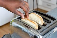 De broodrooster van de roestvrij staalbroodrooster met geroosterd brood voor ontbijt binnen met keuken op de achtergrond Handen v stock fotografie