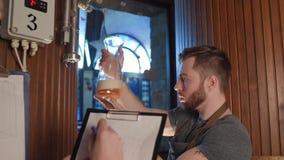 De brouwer controleert vers gebrouwen bier-blikken bij zijn kleur, dichtheid, transparantie op de achtergrond van de brouwerij stock video
