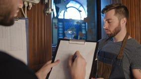 De brouwer controleert vers gebrouwen bier-blikken bij zijn kleur, dichtheid, transparantie op de achtergrond van de brouwerij stock footage
