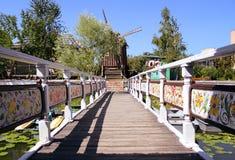De brug over de rivier met een mooi traliewerk dat tot de oude windmolen leidt royalty-vrije stock afbeelding