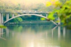 De brug van de boogsteen over het meer Stock Foto
