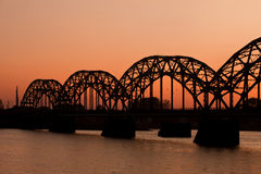 De brug van de spoorweg bij zonsondergang stock afbeelding