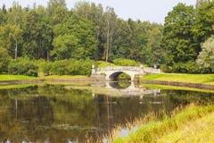 De brug van de Viscontisteen over de rivier Slavyanka in het park Pavlovsk Rusland Stock Afbeelding