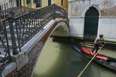 De Brug van gondelierpushing gondola under in Venetië, Italië Royalty-vrije Stock Afbeelding