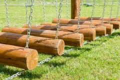 De brug van kinderen van logboeken en kettingen wordt gemaakt die stock fotografie