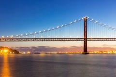 De Brug van Lissabon bij schemer Stock Foto's
