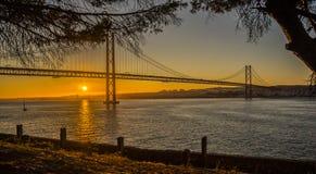 De Brug van Lissabon over de zonsondergang van de tagusrivier van Almada wordt gezien die Stock Afbeelding