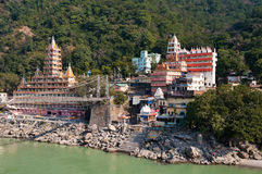 De brug van Tera Manzil Temple en van Laxman Jhula over de rivier van Ganges stock afbeeldingen