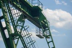 De brugkraan wordt geschoten van onderaan tegen de blauwe hemel en de witte wolken stock foto