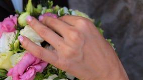 De bruid bekijkt het huwelijksboeket stock footage