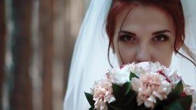 De bruid bevindt zich dichtbij bomen in het bos, brengt een boeket van bloemen om onder ogen te zien en bekijkt de camera, portre stock videobeelden