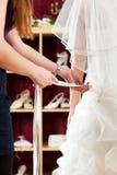 De bruid bij de klerenwinkel voor huwelijk kleedt zich Stock Afbeeldingen