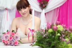 De bruid die witte kleding draagt zit bij lijst stock afbeeldingen