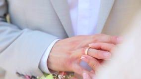 De bruid draagt een huwelijk aan haar echtgenoot stock footage